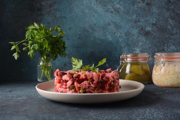 식초 또는 식초. 회색 배경에 흰색 접시에 요리하고 절인 야채, 완두콩, 비트 뿌리를 넣은 전통적인 러시아 레드 샐러드.