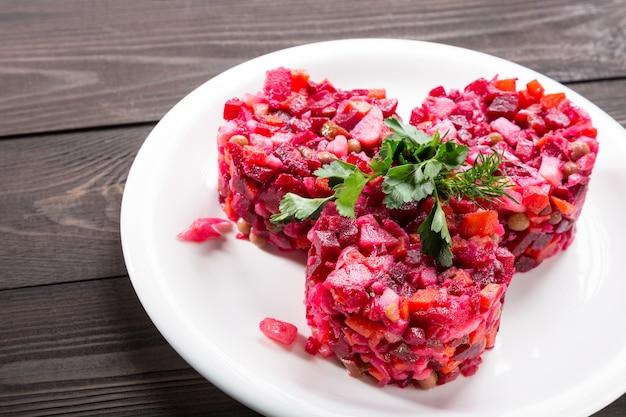 Vinegretの伝統的なロシアのビートサラダと野菜のハーブと白い皿と木製のテーブル