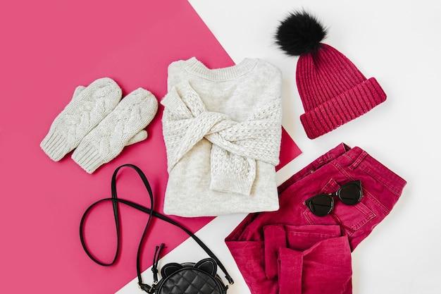 白い背景の上のセーター、ハンドバッグ、ミトンとワインの冬の帽子とズボン。女性のスタイリッシュな秋または冬の服。トレンディな服のコラージュ。フラットレイ、上面図。