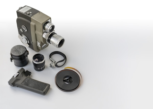 Vintage 8mm camera with 8mm reel and accessories on white background.