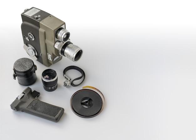 白い背景に8mmリールとアクセサリーを備えたヴィンテージ8mmカメラ。