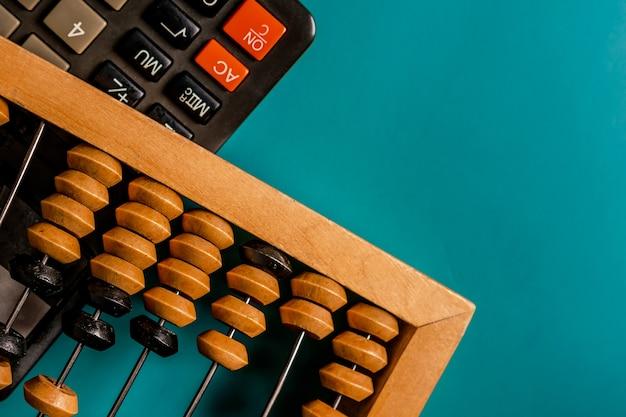 Старинные счеты и современный калькулятор на зеленом