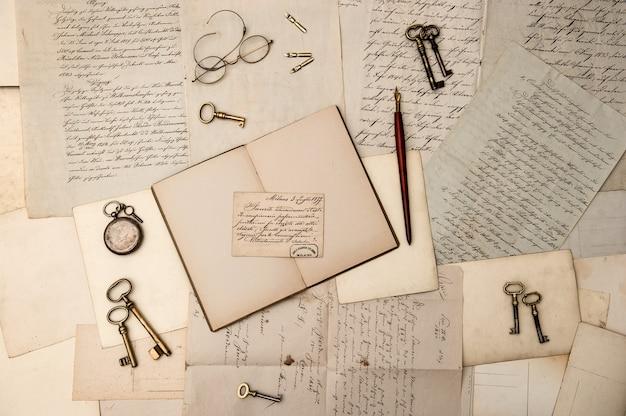 古い手紙やはがきの上にヴィンテージのアクセサリーや開いた本。ノスタルジックな背景