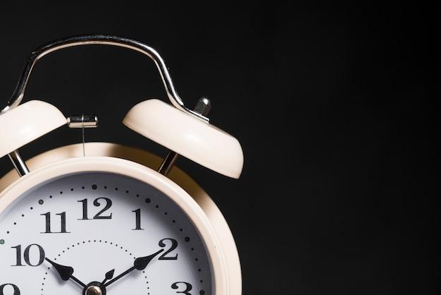 黒の背景にヴィンテージの目覚まし時計