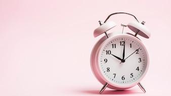 ピンクの背景にヴィンテージの目覚まし時計