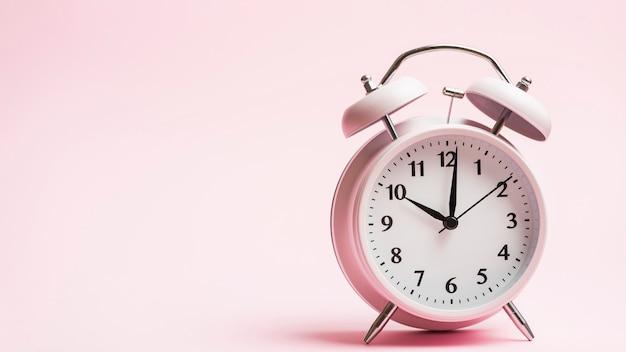 Vintage alarm clock against pink background