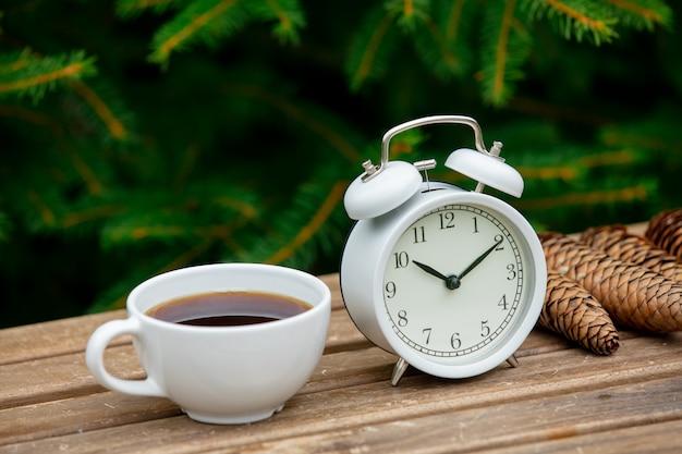 Старинный будильник и чашка кофе на деревянный стол с еловыми ветками на фоне