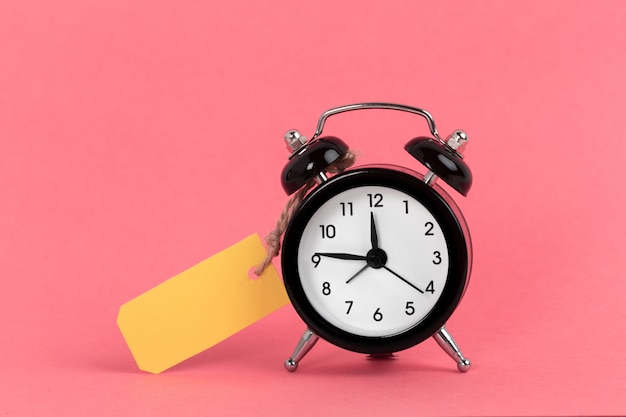 Vintage alarm clock on a bright pink surface