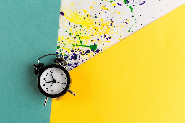 Vintage alarm clock on a creative colorful  with paint sprinkles