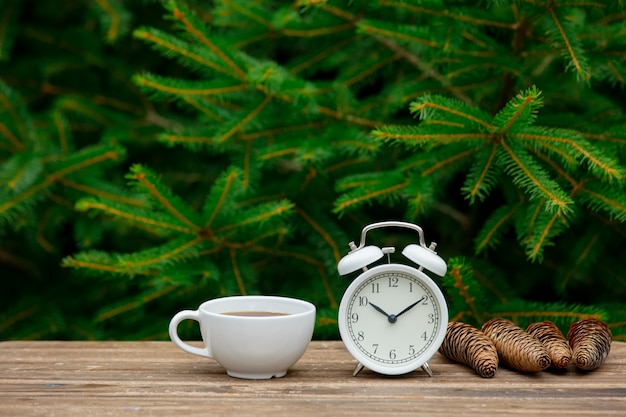 Vintage alarm clock and cup of coffee on wooden table with spruce branches on background