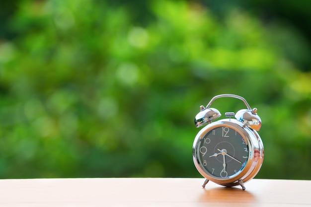 Vintage alarm clock on green burred background.