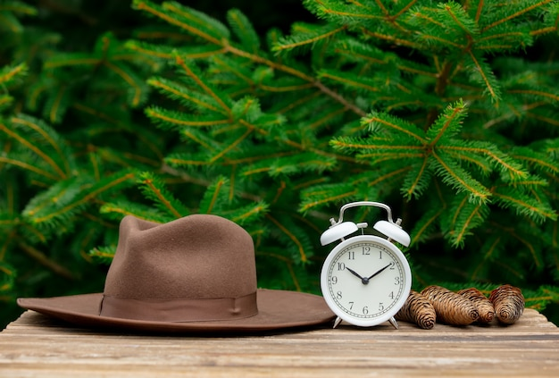 Vintage alarm clock and hat on wooden table with spruce branches on background