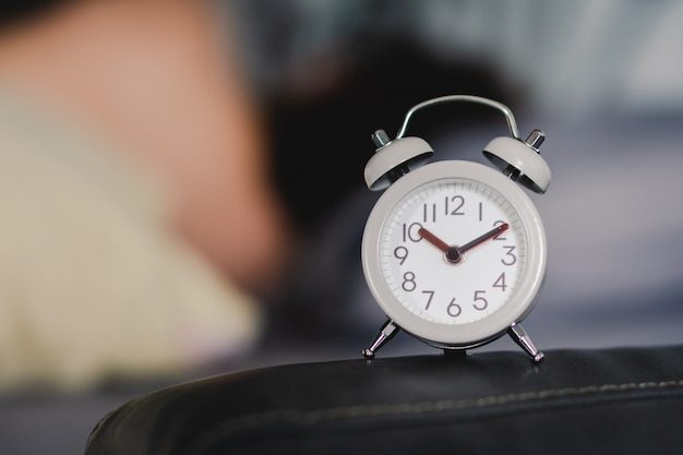 A vintage alarm clock is placed on the head of the bed. conceptual media