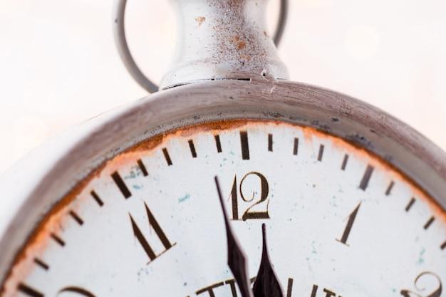 ヴィンテージの目覚まし時計は真夜中を示しています。それは12時、クリスマスとボケ、明るいボケの背景に休日の新年あけましておめでとうございますお祭りのコンセプトです
