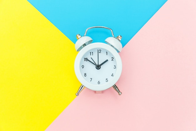 Vintage alarm clock isolated on blue yellow pink pastel colorful trendy geometric background