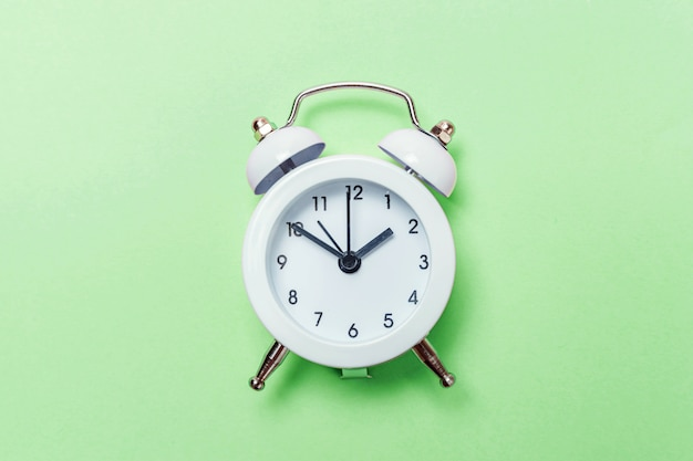 Vintage alarm clock isolated on green pastel background