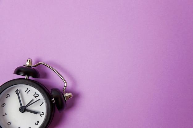Vintage alarm clock isolated on purple
