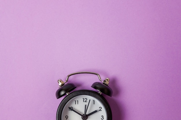 Vintage alarm clock isolated on purple