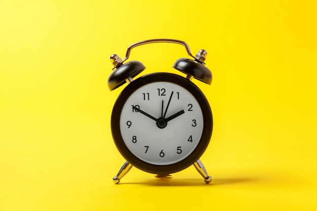 Vintage alarm clock isolated on yellow background