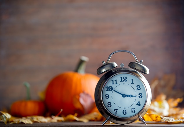 Vintage alarm clock and maple tree leaves with pumpkins