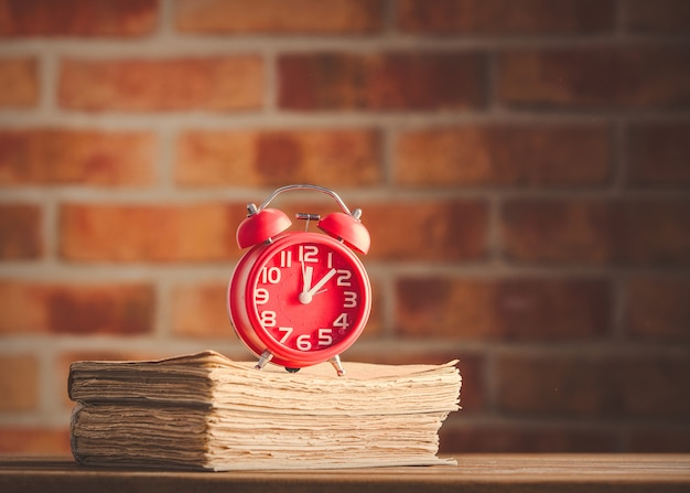 Vintage alarm clock and old books on wooden table