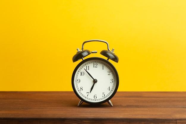 Винтажный будильник на желтом фоне. черный будильник, показывающий утреннее время на столе. концепция времени.