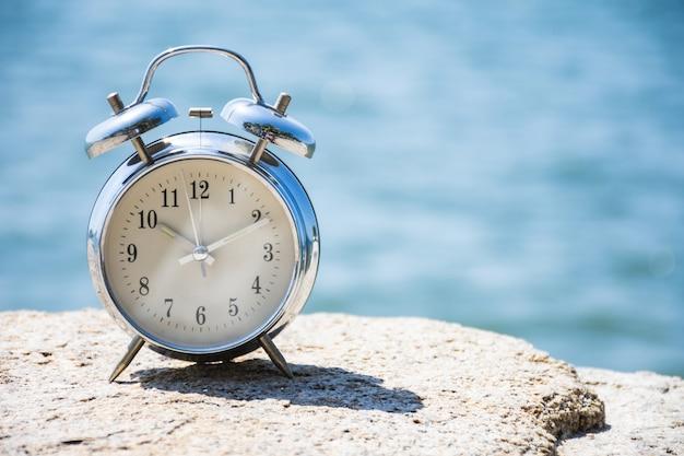 바다 배경이 흐릿한 자연석에 있는 빈티지 알람 시계.