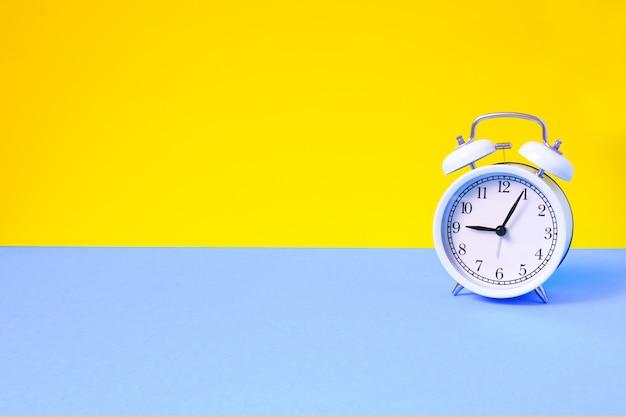 2つのトーンの単色の黄色と水色のテーブルにビンテージの目覚まし時計