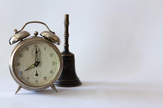 핸드 벨과 흰색 바탕에 빈티지 알람 시계입니다. 선택적 초점입니다. 공간을 복사합니다.