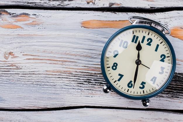 白い木製のテーブルの上のヴィンテージ目覚まし時計。反射ガラス。スペースフラットレイをコピーします。