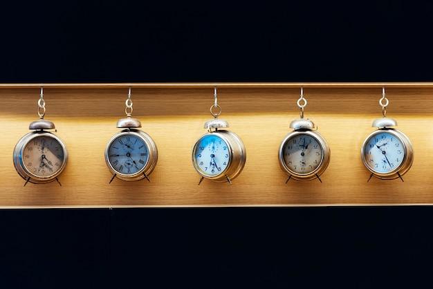 木製の背景にヴィンテージ目覚まし時計。時間の概念。
