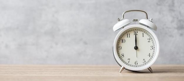 木製のテーブルの背景とテキストのコピースペースにヴィンテージ目覚まし時計。活動、日常、朝、カウントダウン、トレーニング、ワークライフバランスの概念