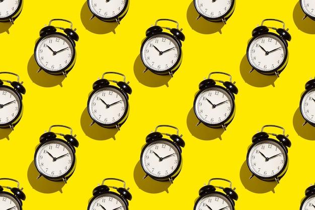 黄色の背景にヴィンテージ目覚まし時計。抽象的なパターン。