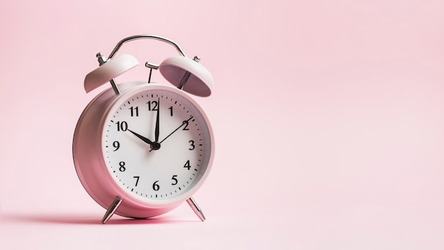 Vintage alarm clock on pink background