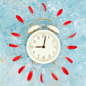Vintage alarm clock and red petals over blue textured background