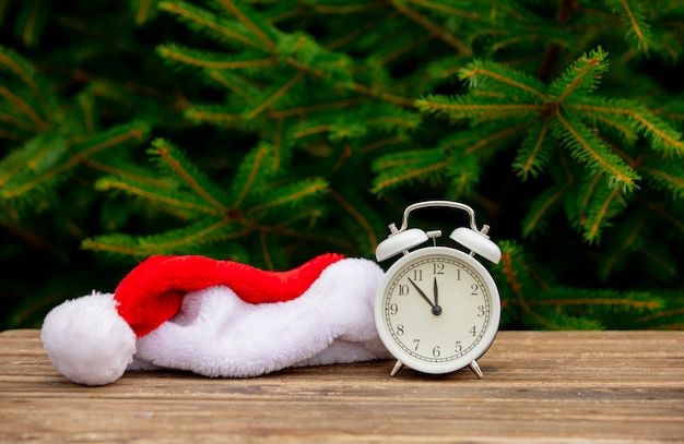 Vintage alarm clock and santa claus hat on wooden table with spruce branches on background