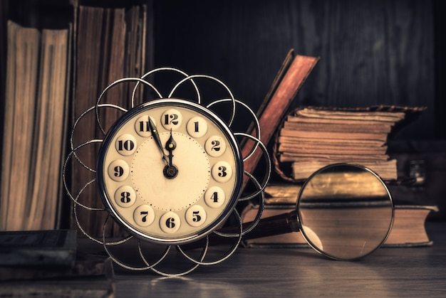 Vintage alarm clock showing five to twelve among old books