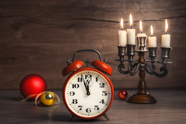Vintage alarm clock showing five to twelve and christmas baubles