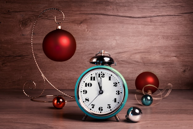 Vintage alarm clock showing five to twelve with christmas baubles