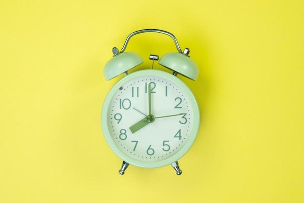 Vintage alarm clock on sweet pastel colored paper