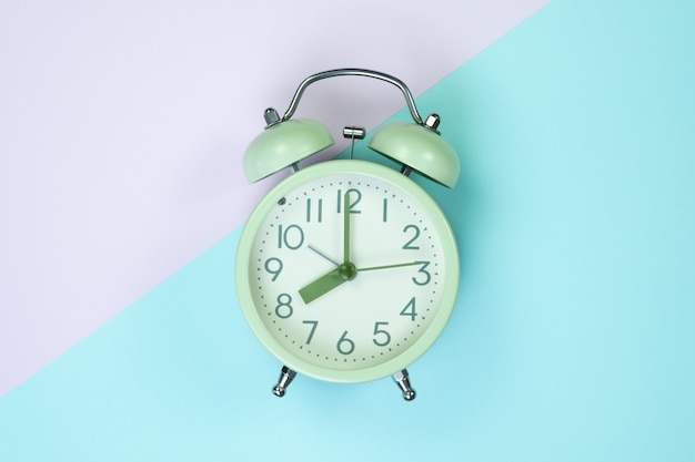 Vintage alarm clock on sweet pastel pape