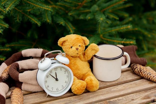 Старинный будильник, плюшевый мишка и чашка кофе на деревянный стол с еловыми ветками на фоне