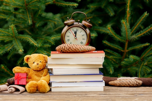Vintage alarm clock, teddy bear and books on wooden table with spruce branches on background