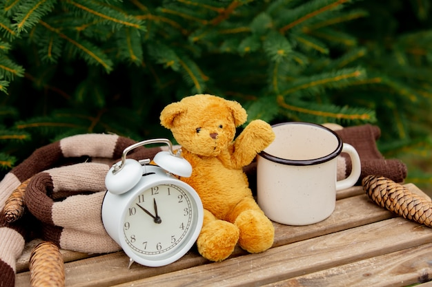 Vintage alarm clock, teddy bear and cup of coffee on wooden table with spruce branches on background
