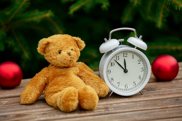 Vintage alarm clock and teddy bear on wooden table with spruce branches on background