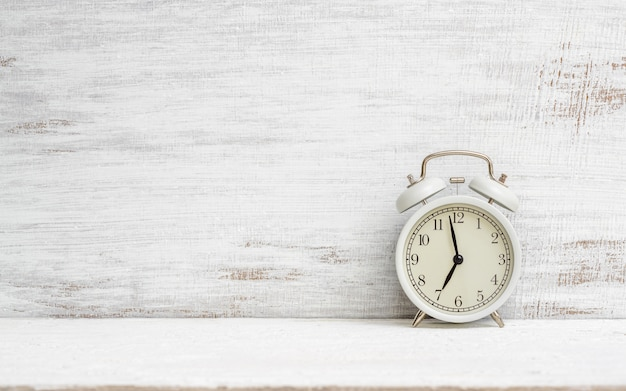Vintage alarm clock on white grunge background