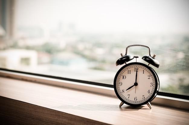 Vintage alarm clock at windows at early morning