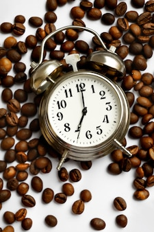 Vintage alarm clock with bells on scattered roasted coffee beans on white