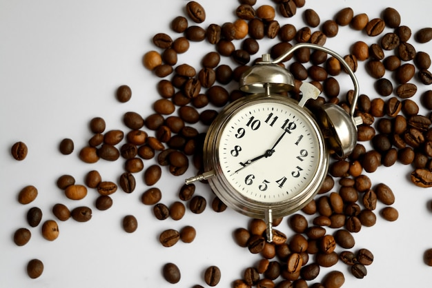 Vintage alarm clock with bells on scattered roasted coffee beans