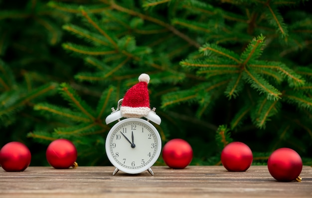 Vintage alarm clock with christmas hat and baubles on wooden table with spruce branches on background